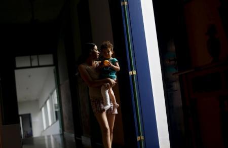 Eliene Almeida, la profesora a cargo de la escuela municipal brasileña de Bento Rodrigues, posa para una fotografía con su bebé en brazos en un hotel para personas desplazadas en Mariana