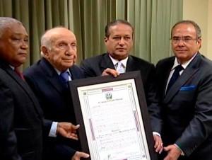 Marino Vinicio Castillo recibe el reconocimiento de manos de los senadores Reinaldo Pared Pérez y Charlie Mariotti.