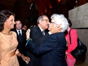 El presidente Danilo Medina besa a la exvicepresidenta de la República y dirigente del PRD, Milagros Ortiz Bosch, mientras observa la primera dama Candy de Medina, al coincidir ayer en la Basílica de  Higüey con motivo de la homilía por el Día de la