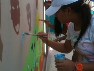 Estudiantes pintan mural en el Aeropuerto de Punta Cana.