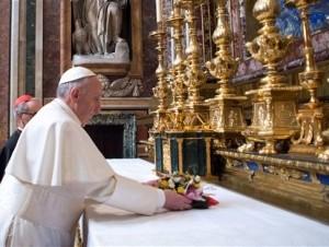 El papa Francisco coloca flores sobre el altar dentro de la Basílica de Santa María la Mayor, en Roma, el jueves 14 de marzo de 2014.