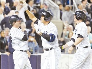 Álex Rodríguez, centro, celebra con J.R. Murphy, izquierda, y Brendan Ryan después de disparar jonrón las bases llenas en el séptimo episodio.