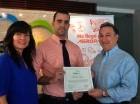 Jaime León y Annie Mesa entregan el certificado a Carlos Fulvio Antonio Céspedes.