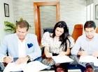 Ejecutivos mientras firman el acuerdo.