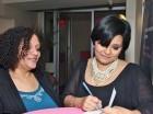 La escritora Lourdes Batista mientras firma uno de sus libros.