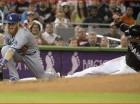 Christian Yelich, derecha, de los Marlins de Miami, se barre en tercera base mientras Justin Turner, de los Dodgers de Los Angeles, no logra quedarse con la pelota en el primer inning del juego en Miami.