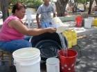 Una mujer llena cubetas de agua en un barrio de Santiago.