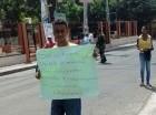 Uno de los estudiantes becados de Villa González, sostiene un cartel solicitando ayuda.