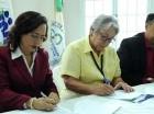Nathalie María y Altagracia Guzmán Marcelino firman el acuerdo.