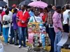 Una haitiana hace su día vendiendo en la calle Francisco Henríquez y Carvajal a sus compatriotas que se regularizan.