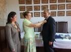 Miguelina Acosta y Margarita Rodríguez colocan un botón del Club Rosario al presidente de SDB, Dennis R. Simó.