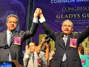 Danilo Medina y Leonel Fernández levantan sus brazos en señal de la victoria durante el acto de proclamación del primero como candidato presidencial.