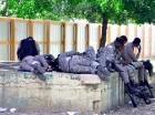 """Agentes del Comando Cibao Central toman sus """"pavitas"""" mientras otros hablan por teléfono ."""