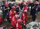 Equipos de rescate rodean el cuerpo de una de las víctimas recuperado de un deslizamiento de tierra en Santa Catarina Pinula, en las afueras de la ciudad de Guatemala, el viernes 2 de octubre de 2015. Por lo menos siete personas murieron y 25 resultaron