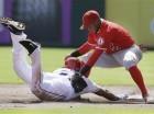 El torpedero dominicano Erick Aybar, de los Angelinos de Los Angeles, no logra aplicar el out a su paisano Adrián Beltré, de los Rangers de Texas, quien se lanza hacia la segunda base, en la primera entrada del partido en Arlingon, Texas.