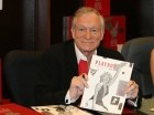 En esta imagen del 15 de novienbre del 2007, Hugh Hefner firma ejemplares del calendario Playboy. Playboy no publicará más fotografías de mujeres desnudas como parte de un nuevo diseño, anunció el 13 de octubre del 2015 la revista que se publica desd