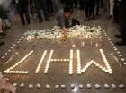 En esta imagen de archivo, tomada el 25 de julio de 2014, un miembro de la tripulación de Malaysia Airlines deposita una vela junto a velas que forman las MH17 tras un servicio multireligioso por las víctimas del avión de la compañía derribado en Ucr