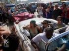 Seguidores le toman fotos a la cantante pop Rihanna (con un pañuelo verde) mientras viaja en un auto clásico estadounidense por La Habana, Cuba.