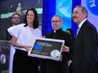 El presidente Danilo Medina y la licenciada Lina García, presidenta de la AIREN, entregan una placa de reconocimiento a monseñor Agripino Núñez Collado, como parte de los actos de celebración de los 30 años de la entidad empresarial.