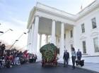 La primera dama, Michelle Obama, centro, con sus perros Bo y Sunny, recibe al árbol navideño oficial de la Casa Blanca en Washington, el viernes 27 de noviembre de 2015.