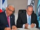 Los funcionarios al firmar el acuerdo.