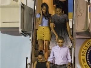 El presidente estadounidense Barack Obama, arriba a Honolulu, Hawaii, con su esposa Michelle, al fondo a la derecha, y sus hijas Sasha, al frente a la izquierda, y Malia, para el inicio de las vacaciones navideñas.