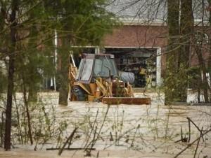 Inundaciones rodean equipo de construcción en un patio en el condado Madison, en Alabama, el día de Navidad, el viernes 25 de diciembre de 2015. Un clima cálido fuera de lo habitual en la temporada contribuyó a que hubiera severas tormentas el viernes