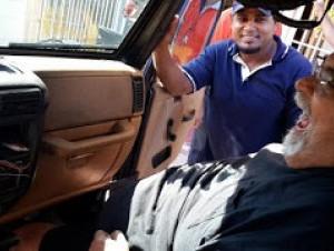 El cantautor Anthony Ríos sentado dentro de su vehículo luego que le robaran el radio y otras pertenencias en Pedernales.