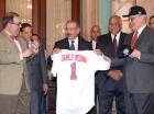 El presidente Danilo Medina recibe de Leonardo Matos Berrido (der.), presidente de la Liga Dominicana de Béisbol (Lidom), y Felipe Vicini, presidente de los Leones del Escogido, la chaqueta que usará el equipo criollo para la Serie del Caribe.