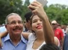 El presidente Danilo Medina sonríe junto a una joven mientras se hacen una selfie.