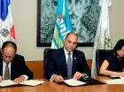 Lidio Cadet, Enrique Ramírez Paniagua y Rosa Rita Álvarez firman el acuerdo.