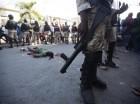 Miembros de la Policía Nacional rodean el cadáver de Neroce R. Ciceron, un ex capitán del abolido ejército de Haití, tras ser golpeado y apedreado por manifestantes antigubernamentales en Puerto Príncipe.