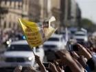 Una persona ondea una bandera y otras alzan sus celulares mientras el convoy del papa Francisco avanza hacia la Basílica de Guadalupe, en Ciudad de México, el sábado 13 de febrero de 2016. La visita de cinco días del pontífice incluye la visita al te