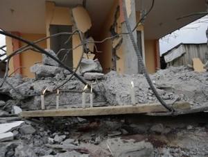 Velas encendidas delante de un edificio derrumbado como un tributo a las víctimas de un terremoto de magnitud 7,8 en La Chorrera, Ecuador, el lunes 18 de abril de 2016. (Foto AP/Dolores Ochoa)