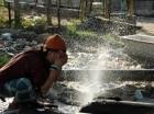 Un aldeano indio humedece su rostro con agua de una tubería rota en el distrito Samba, cerca de 40 kilómetros (25 millas) de Jammu, India.