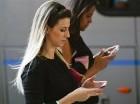 Mujeres revisan sus teléfonos celulares mientras caminan por Sao Paulo, Brasil el lunes 2 de mayo de 2016.