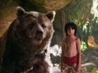 En esta imagen difundida por Disney, Mowgli, interpretado por Neel Sethi, derecha, y el oso Baloo actúan en una escena de El libro de la selva.