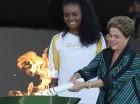 La presidenta brasileña Dilma Rousseff, derecha, enciende la antorcha olímpica al lado de la voleibolista Fabiana Claudino durante una ceremonia tras la llegada de la llama olímpica a Brasil el martes, 3 de mayo de 2016, en Brasilia.