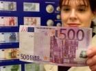 En esta imagen del 1 de septiembre de 2001, Aline Heurley, de Flensburg, mira un billete de 500 euros frente a un poster que anuncia la nueva moneda.