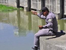 Un agente de la PN pescando, en busca de la comida