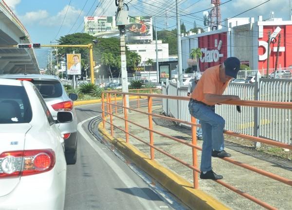 Las barreras colocadas por la alcaldía para dividir las aceras de las calles, y así proteger a los transeúntes son burladas por este señor, que expone su vida al saltar las barandas, en el tramo Juan Palbo Duarte, esquina Estrella Sadhalá.